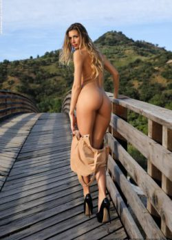 Sexy blonde glamour woman Claudia a nude walk on the bridge
