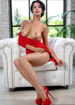Marvelous busty babe Nadine removes her sexy red dress to pose nude